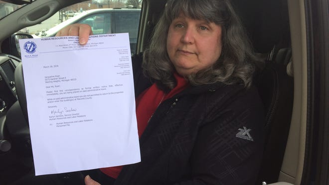 Deputy Macomb County Clerk Jackie Ryan holds up a letter stating she's been placed on administrative leave March 28 in the wake of County Clerk Karen Spranger's ouster. Shortly after, temporary acting county clerk Kathy Brower dismissed Ryan from her position.