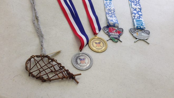 A progression of Jim Miner's snowshoe racing medals, from the state/local level, through to international silver.