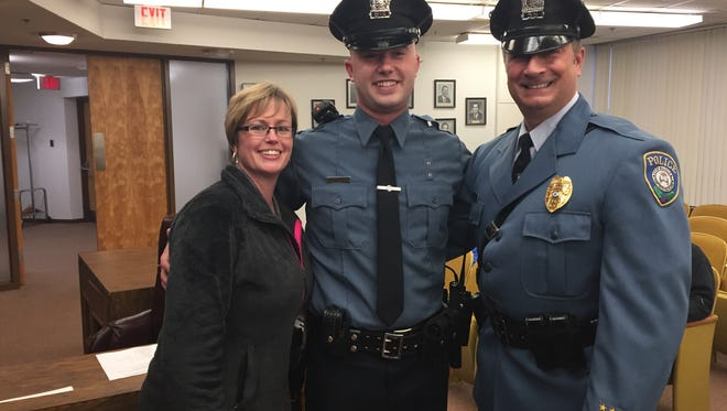 """Class II Special Officer Tyler Loteck (center) is the newest member of the Millville Police Department. Loteck was sworn in at Tuesday night's City Commission meeting. He is flanked by his mother Tiffany and father, Millville Officer William """"Tony"""" Loteck."""
