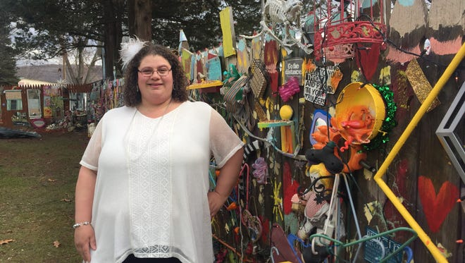 Carita Puglisi, of Binghamton, uses her mixed media backyard fence to spread optimism.