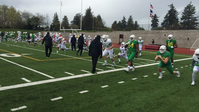 Oregon football players warm up before practice Saturday in Portland.