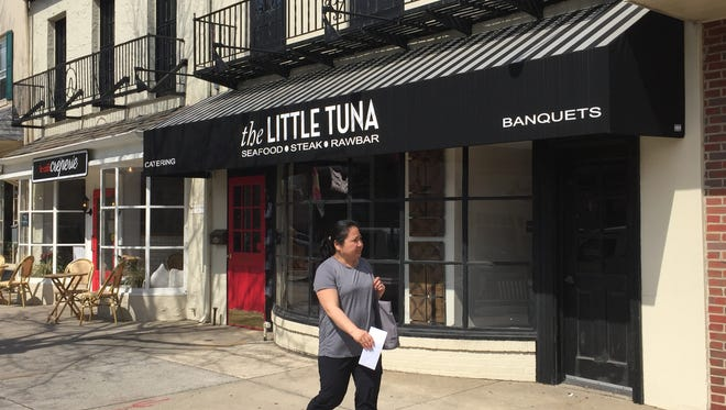 A woman passes the former home The Little Tuna on Kings Highway in Haddonfield.