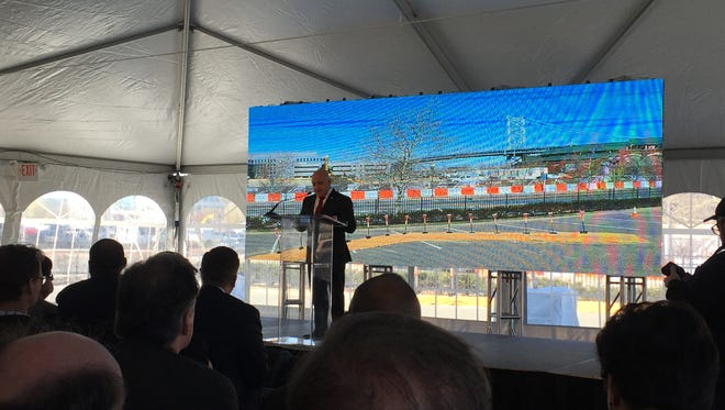 Camden Mayor Frank Moran speaks at the groundbreaking for 11 Cooper Street as a giant video screen behind him shows the ongoing construction.