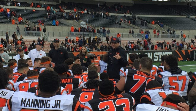 OSU players huddle around head coach Jonathan Smith after the annual spring game at Reser Stadium on April 28, 2018.