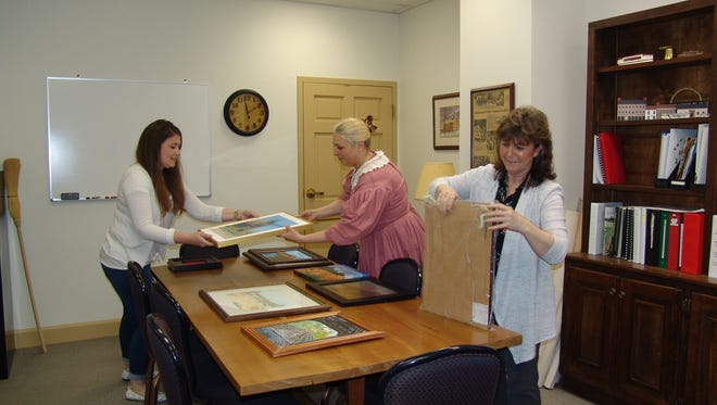 Jandi Adams, Roscoe employee Stacie Stein and Lynda Daniel organize paintings by members of the Artist Collective that will be on exhibit during An Evening with the Arts.