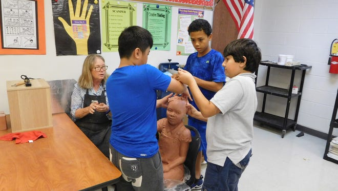 Meale looks on while Conley students add hair to the little girl sculpture.