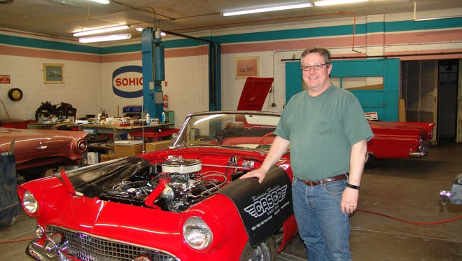Jim Brown of Classic Auto Supply Company  stands by a T-Bird in his restoration shop. The small business has 13 full-time employees.