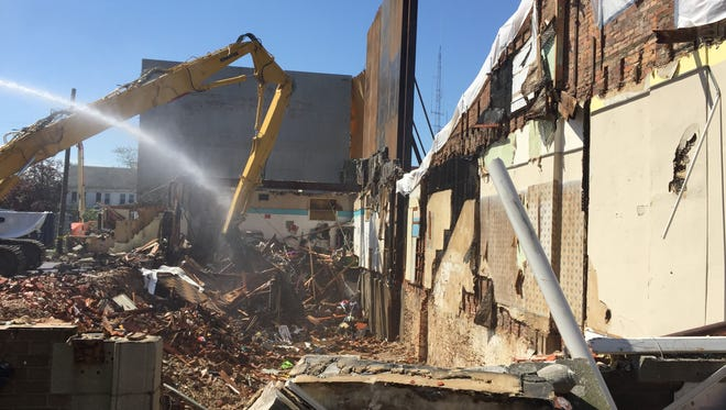 Water keeps dust down on Tuesday as an excavator digs into piled debris in the basement of what until recently was a three-story building at 109 E. Main St. in Millville.