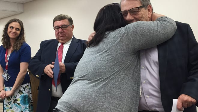 Kailey Krebs hugs Municipal Court Judge Jerry Ault during Wednesday's drug court graduation. At left are Nikki Cherry and Judge Frank Ardis.