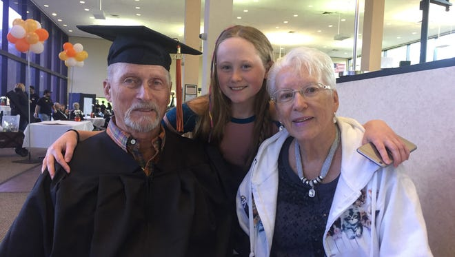 Robert Fitch, left, his great-granddaughter Lexi, and wife, Evelyn, before Fitch walked across the stage at RIT to receive his diploma. He first enrolled in 1959.