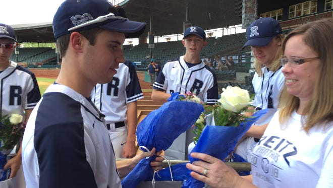 Reitz baseball player Camden Hancock gives his mom, Sara Springer, a white rose in senior night at Bosse Field Tuesday evening.