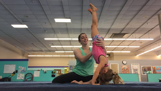 Galaxy Gymnastics coach Emily Walstrum helps Shaylin McCarthy, 3, perform a handstand on Tuesday, May 15. The studio replaced the former Hancock Fabrics in Salisbury's Twilley Centre.