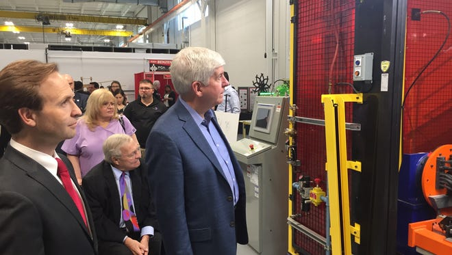 From left, Michigan Lt. Gov. Brian Calley and Gov. Rick Snyder view a robotic welder Thursday in Auburn Hills, joined by Oakland County Executive L. Brooks Patterson (behind them).