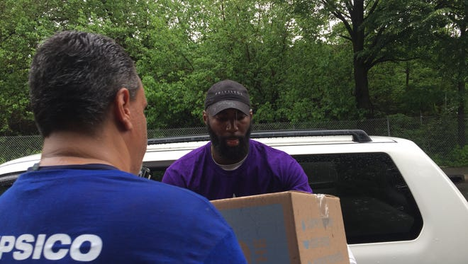 Eagles safety Malcolm Jenkins helps load boxes of food and toiletries into Clemente Crespo's car Thursday at the Get Read Fest in Camden.