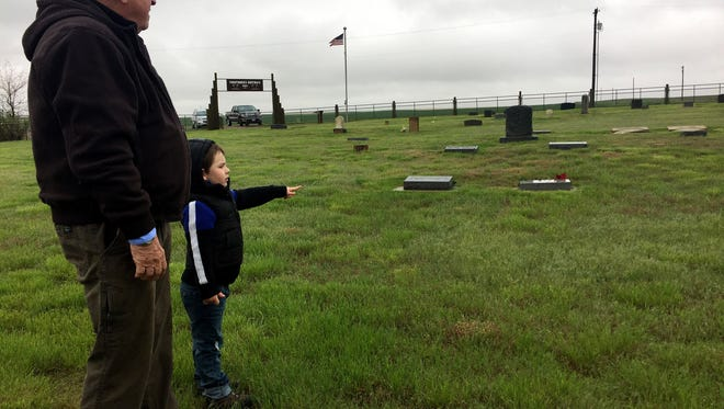 Dennis Nottinghamand Henry, 4, walk through the Carter Cemetery, where some graves, even for persons unknown, have new markers thanks to a community project.
