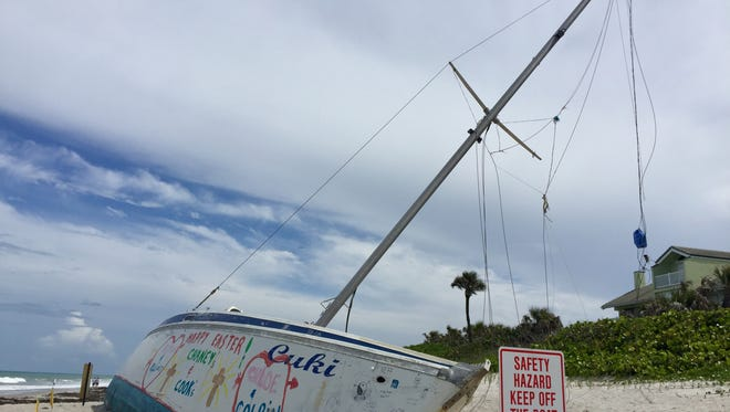 """Brevard County officials have posted """"Safety Hazard Keep Off The Boat"""" signs around the grounded sailboat atSpessard Holland South Beach Park."""
