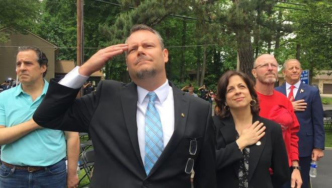 Naval reservist Darryl Smith salutes the raising of the flag from half-staff next to his wife, Maryann, after a Memorial Day ceremony at which his son, Kenneth, was remembered. Kenneth was a sailor killed on the Navy destroyer USS John McCain last year after a collision with an oil tanker in the Pacific near Malaysia in the Global War on Terror.