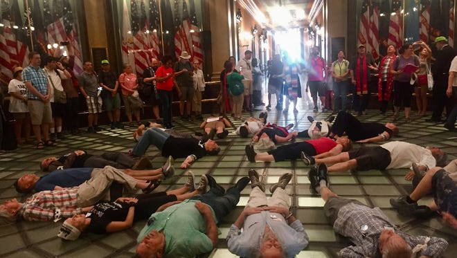 Protesters for the Michigan Poor People's Campaign lie down on the rotunda of the Michigan capitol Tuesday, May 29, 2018 in Lansing, Mich., as part of a die-in to protest war and militarism. Nineteen were arrested and received trespassing citations for not leaving when ordered. (AP Photo/Alice Yin)