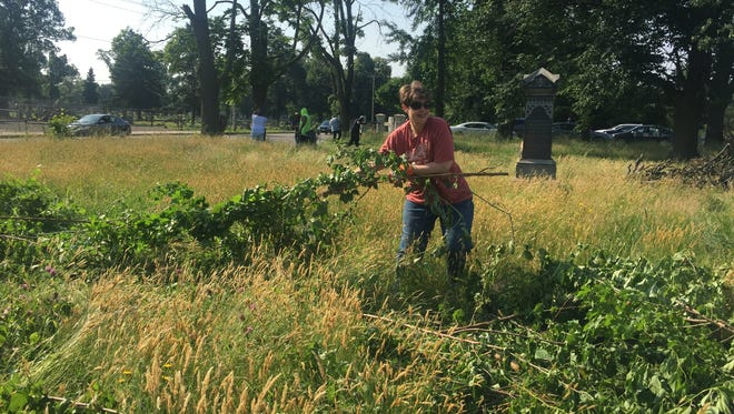Colleen Mayhew of Oaklyn drags a branch away at Evergreen Cemetery in Camden.