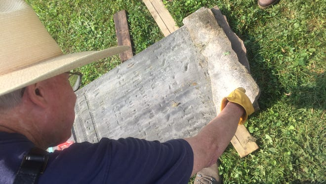 Lewis Poe examines a piece of a thought missing fragment of a historic marker on June 9.