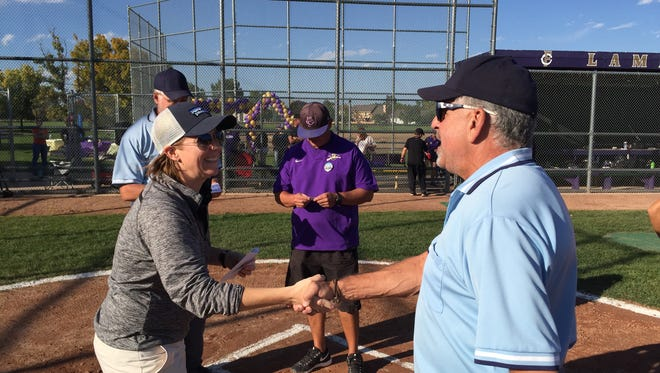 Fort Collins umpire Elliott Finkelstein shakes the hand of a coach during a high school game last season.