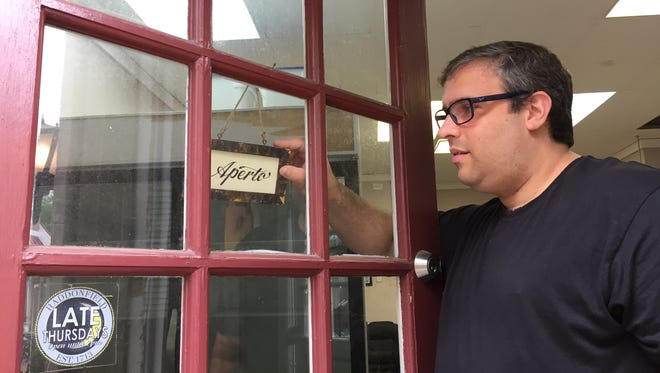 Marcello De Feo turns the sign on Valente's Italian Specialties door to 'aperto,' or open. The market at Kings Court will open for business in the next few weeks.