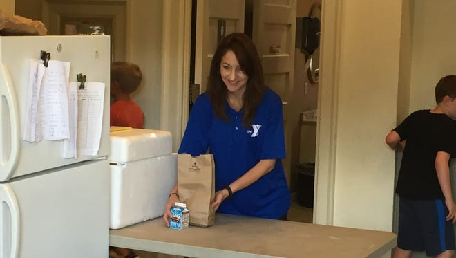 Mary Newhouse of the Lebanon Valley YMCA hands out free lunches to children in Lebanon.
