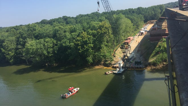 Rescue workers try to help a woman who jumped from the McClure Bridge over the Cumberland River on Friday morning.