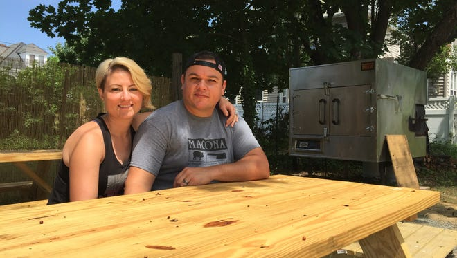 Natalie and Cory Reuss sit at a picnic table near the smoker at their new restaurant, Macona BBQ in Collingswood.