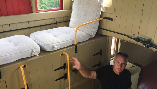 Howell Area Historical Society's vice president Mike Mason grabs a ladder railing in the society's restored 1888 Grand Trunk Western Railroad caboose in downtown Howell, on Wednesday, July 18, 2018.
