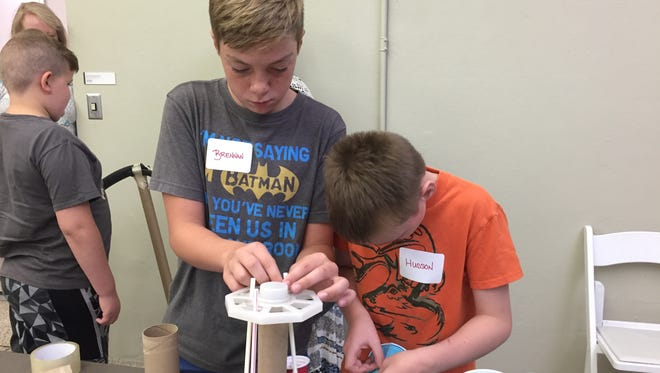 Brennan, 10, and Hudson, 8, design a rotating swing ride, instead of the traditional roller coaster.