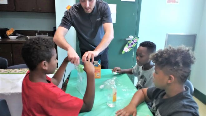 Staffer Rob Risley guides a STEM project at the Boys & Girls Club of Vineland's Carl Arthur Center.