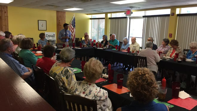 Chintan Desai (standing) address a group of Baxter County Democrats at the Lake Country CookHouse in Mountain Home on July 25. Desai is challenging Republican incumbent Rick Crawford in November to represent the state's 1st District in Congress.