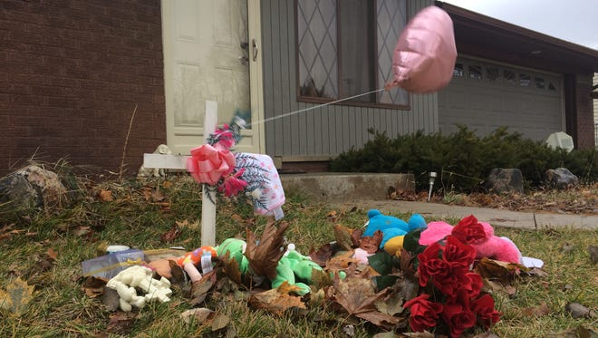 A makeshift memorial is set up Monday, Nov. 24, 2014, at an Oxford Township home where Daryne Gailey, 29, and his infant daughter Charley Hendrick were found dead Sunday morning.