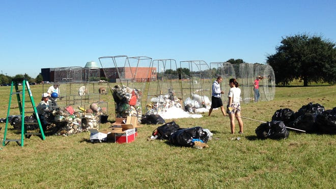 """Volunteers work to put together eight-foot-tall chicken wire letters spelling """"#YARDWORK,"""" which are now stuffed with trash collected from the streets by thousands of volunteers on Saturday for Make a Difference Day."""