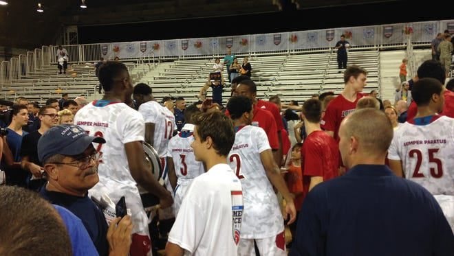 Louisville players take photos and celebrate after beating Minnesota