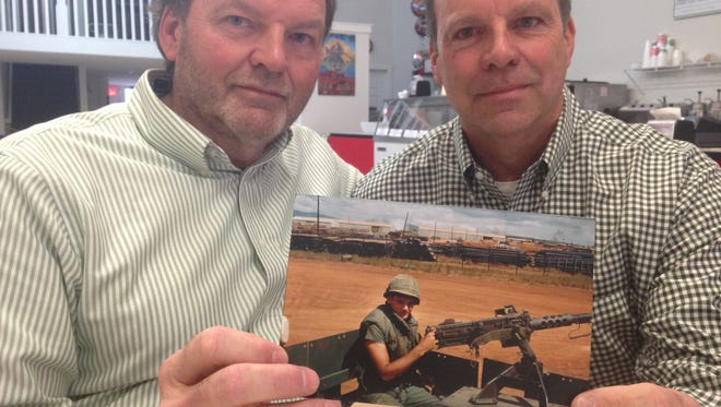 Tom (left) and Jeff Braatz, brothers of the late Curtiss Braatz, hold up a picture of the Charlotte High School graduate and Vietnam solider who was killed in action during the war at the age of 19. The family will donate his medals, awarded after his death, to the school on Veteran's Day, Nov. 11.