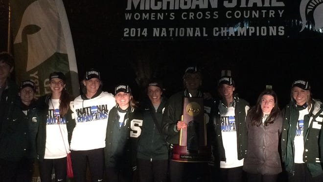 Members of the MSU women's cross country team pose for a picture with the national championship trophy after returning home Saturday night.