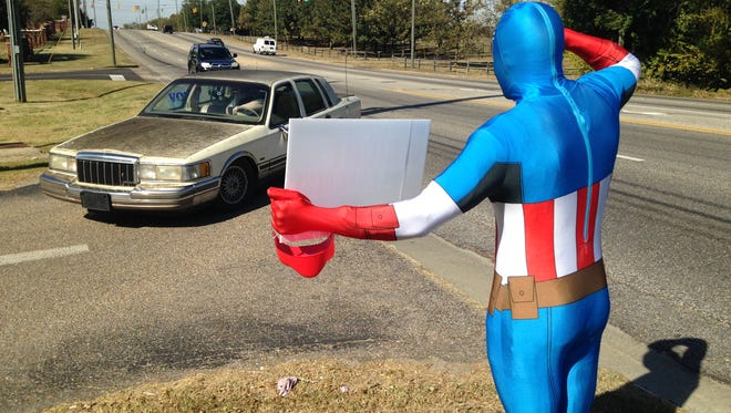 Candidate Erick Wright, dressed as Captain America, salutes cars as they arrive at the polls in Montgomery.