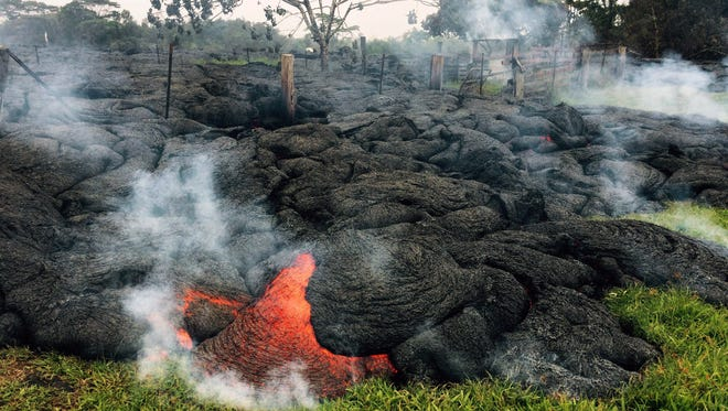 This Oct. 26, 2014 photo provided by the U.S. Geological Survey shows the lava flow front of from an eruption that began the June 27, as the front remains active and continues to advance towards the northeast threatening the town of Pahoa on the Big Island of Hawaii. Dozens of residents in this rural area of Hawaii were placed on alert as flowing lava continued to advance. Authorities on Sunday, Oct. 26, 2014 said lava had advanced about 250 yards since Saturday morning and was moving at the rate of about 10 to 15 yards an hour, consistent with its advancement in recent days. The flow front passed through a predominantly Buddhist cemetery, covering grave sites in the mostly rural region of Puna, and was roughly a half-mile from Pahoa Village Road, the main street of Pahoa. (AP Photo/U.S. Geological Survey)