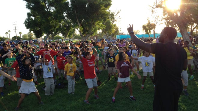 Former NFL player and La Quinta High School graduate Jonathan Ingram leads Cielo Vista Charter School students in warm up exercises before the kids started walking from Demuth Park in Palm Springs to their school on Paseo Dorotea on Wednesday, Oct. 8, 2014.