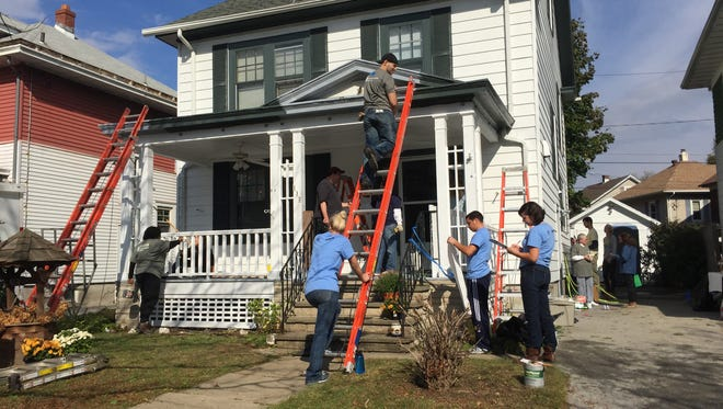 Volunteers from the Poughkeepsie Journal, Central Hudson Gas & Electric. Corp. and United Way of the Dutchess-Orange region help a City of Poughkeepsie homeowner with repairs in a project organized by Rebuilding Together Dutchess County.
