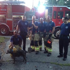 Farmington Hills firefighters who rescued Maxine took a breather with the dog that had been trapped in a sink hole.