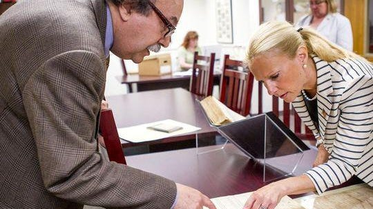 Monmouth County Archivist Gary Saretzky and Monmouth County Clerk Christine Giordano Hanlon look through a volume of Military Petitions For Naturalization from 1918-19.