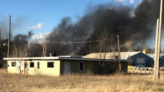 Officials say a fire that destroyed a storage building Monday was started when a suspected burn pile got out of control and became a wildfire.