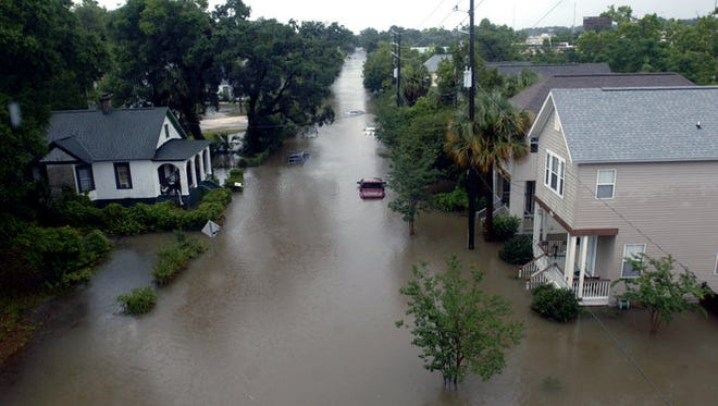 In this June 9, 2012 photo, homes on Guillemard Street are inundated with floodwaters following heavy rains in downtown Pensacola, Fla. The National Weather Service said 13.11 inches fell on Pensacola over 24 hours, coming close to the city's all-time record of 15.29 inches set in 1934, causing what could be millions of dollars in flood damage in the Pensacola area alone with more rain on the way.