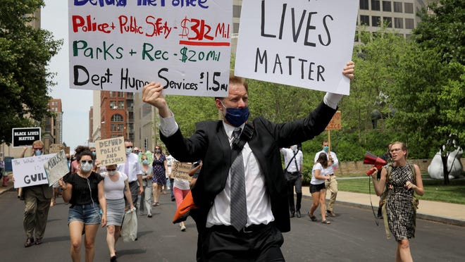 Matthew Mahaffey, a lawyer with the Missouri Public Defenders, leads a protest march with Erika Wurst, right, in favor of Black Lives Matter on Monday, June 7, 2020, with about 100 of his colleagues, staff and supporters from the  appellate courthouse to the the Thomas F. Eagleton U.S. Courthouse in downtown St. Louis.