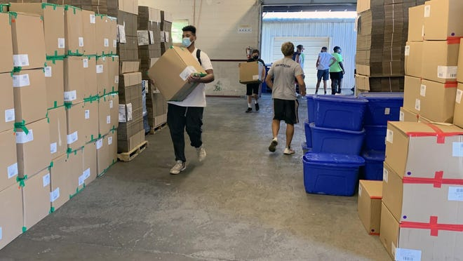Truman High School football players help load boxes of socks from a truck into the warehouse at Community Services League in Independence Monday. Truman performed the task for the charity like their crosstown rival William Chrisman had done the week before after Bombas Socks donated them for use with the needy in Eastern Jackson County.