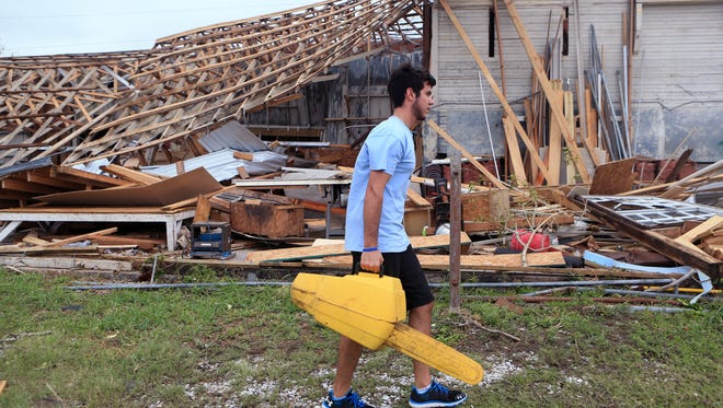 Raymond Valenzuela helps his dad clean up a shop owned by his grandfather in Rockport, TX on Sunday, August 27, 2017 following Hurricane Harvey.
