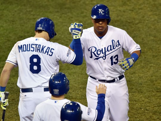 Oct 21, 2014; Kansas City, MO, USA; Kansas City Royals catcher Salvador Perez (13) celebrates with third baseman Mike Moustakas (8) after hitting a solo home run against the San Francisco Giants in the 7th inning during game one of the 2014 World Series at Kauffman Stadium. Mandatory Credit: Peter G. Aiken-USA TODAY Sports